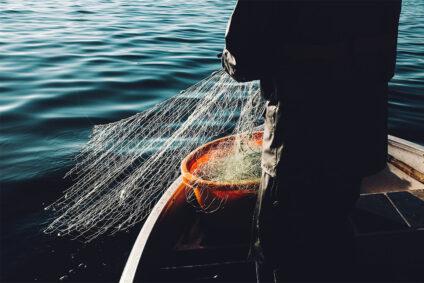 Fischer wirft ein Netz aus.