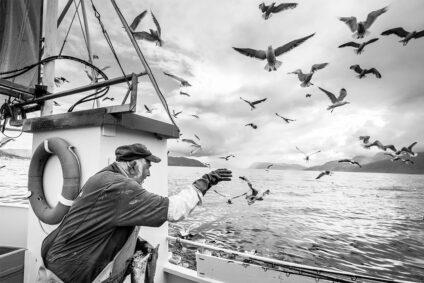 Schwarz-Weiß-Bild eines Fischers im Boot.