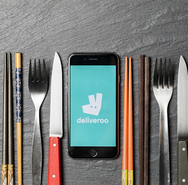 Smartphone zeigt das Deliveroo-Logo an, rechts und links davon liegt Besteck.