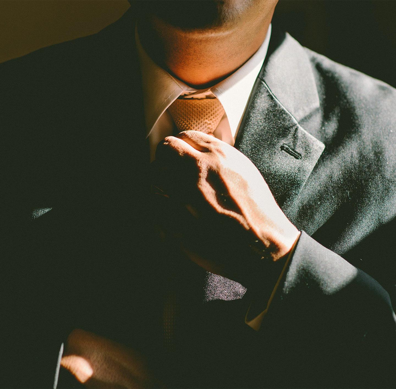 Ein Mann im Anzug richtet seine Krawatte.
