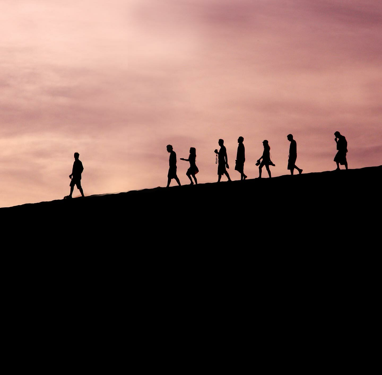 Eine Gruppe Menschen in der Abenddämmerung auf der Kuppe eines Hügels.