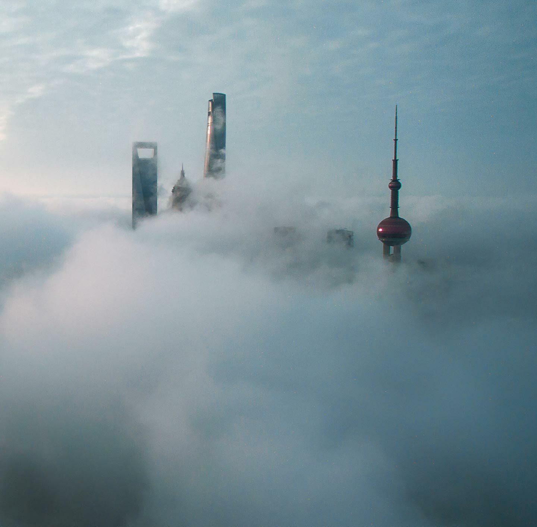 Die Dächer von Hochhäusern ragen zwischen Wolken hervor.