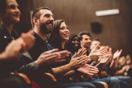 Menschen in einem Saal applaudieren begeistert.