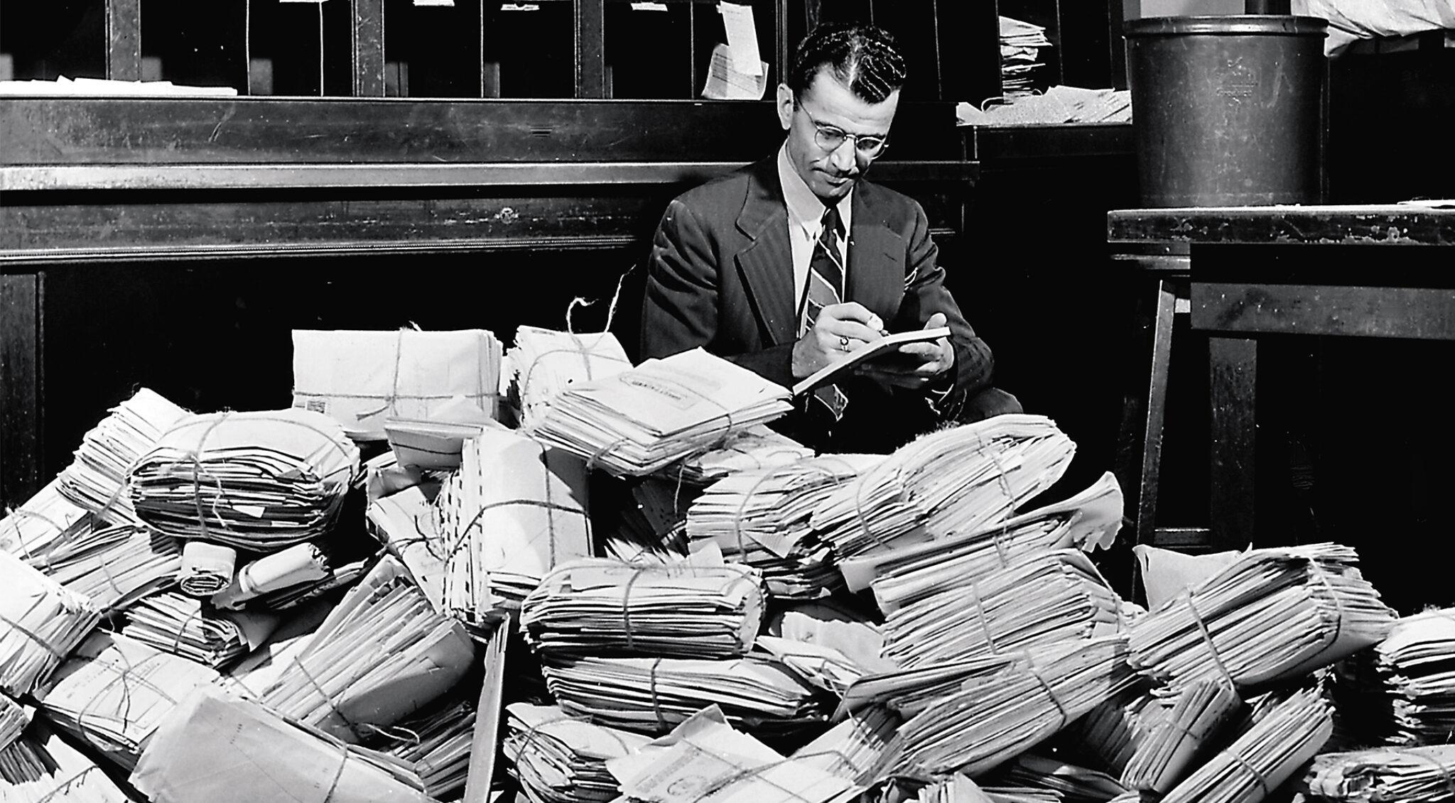 Altes Bild von einem Mann, der umgeben von Briefen mit einem Füller schreibt.