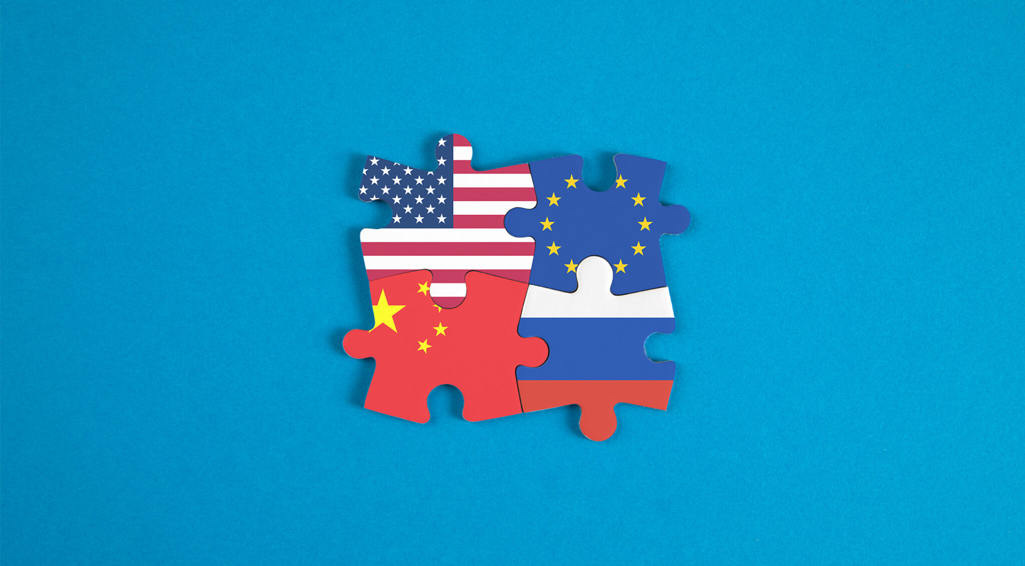 Die Flaggen der USA, China, Europa und Russland als Puzzleteile ineinander gesteckt.