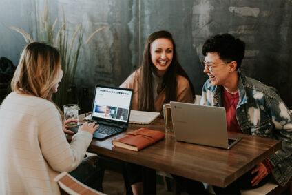 Drei Frauen arbeiten und lachen gemeinsam.