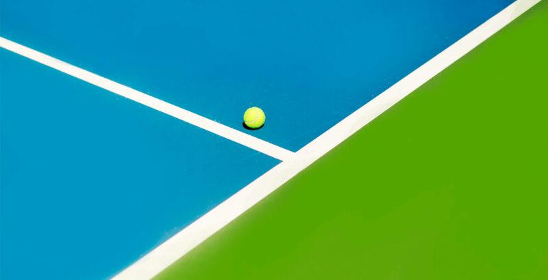 Ein Tennisball auf einem farblich grün-weiß-blau abgesetztem Feld.