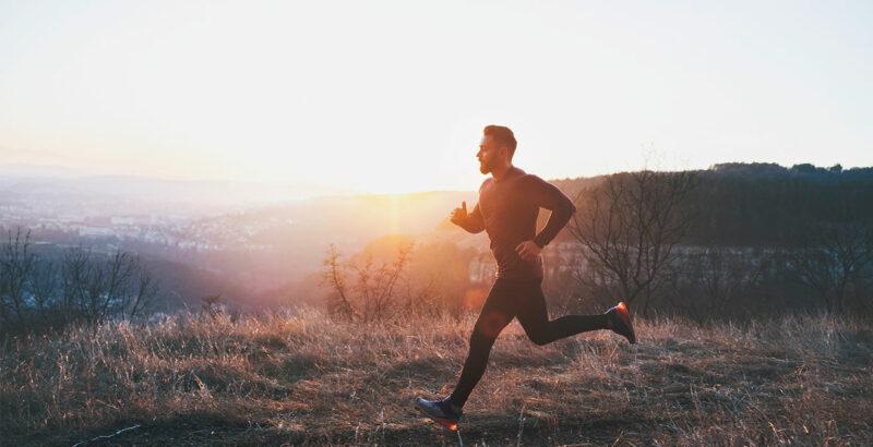 Junger Mann beim Joggen, im Hintergrund der Sonnenaufgang.
