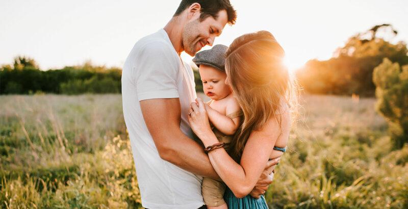 Junge Eltern mit kleinem Kind auf dem Arm.