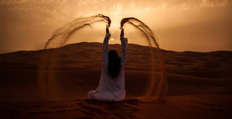 Frau sitzt in der Wüste und wirft Sand in die Luft.