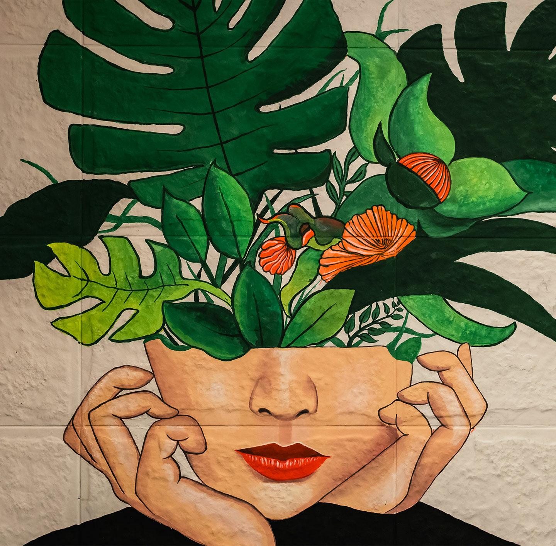 Illustration einer Frau, der Pflanzen aus dem Kopf wachsen.