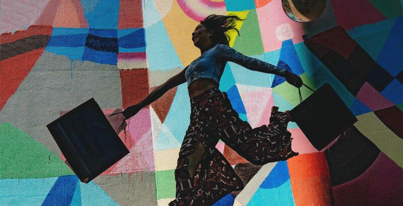 Eine Frau mit Einkaufstüten springt vor einer bunt bemalten Mauer in die Luft.