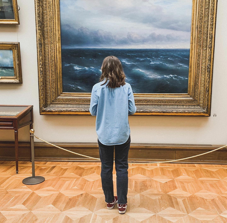 Frau steht in einem Museum vor einem Bild.