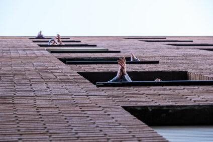 Blick von unten auf eine Hauswand, an mehreren Fenstern klatschende Menschen.