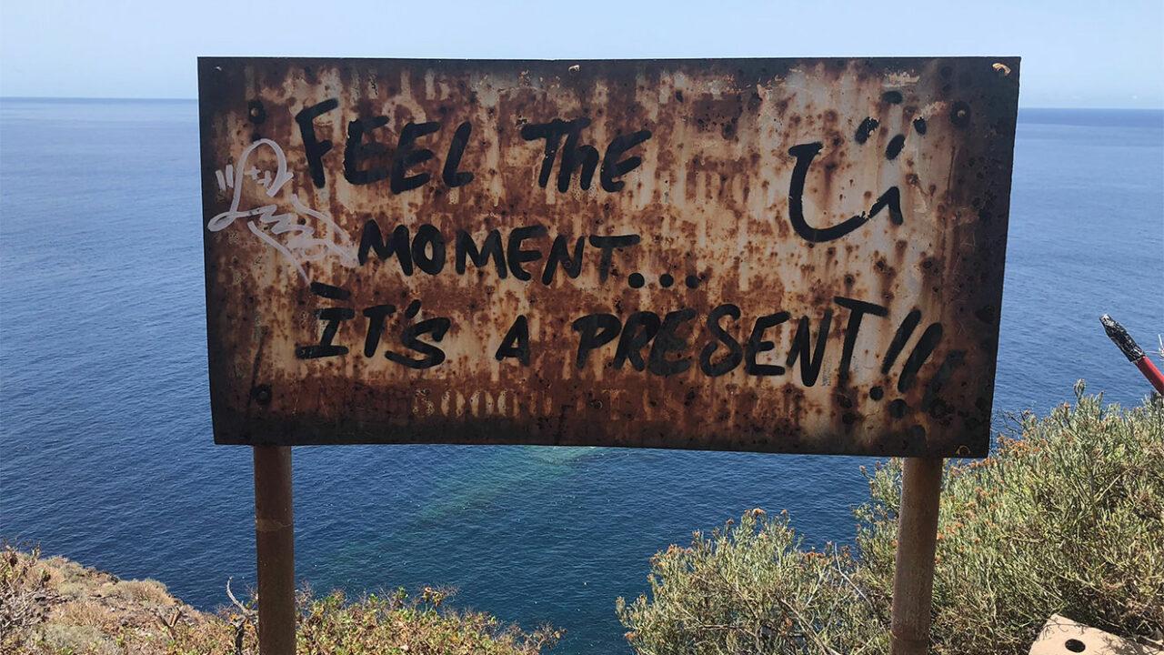 """Altes Schild mit der Aufschrift """"Feel the moment... it's a present!""""."""