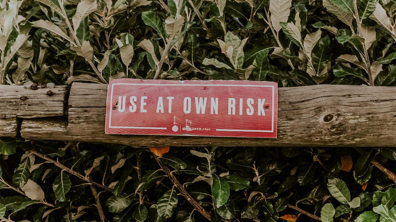 """Schild mit der Aufschrift """"Use at own risk"""" an einem Holzzaun."""