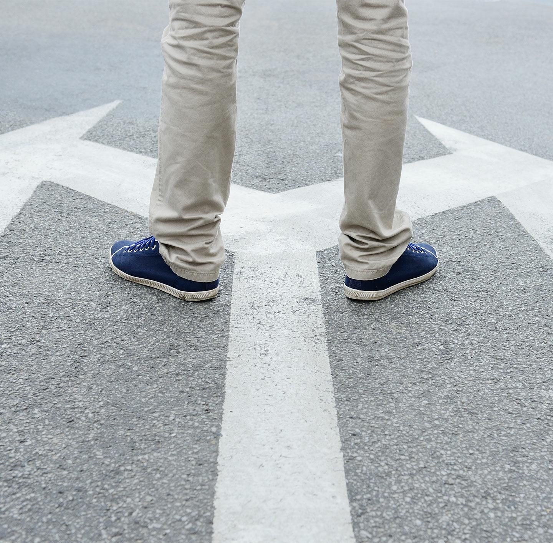 Mann steht vor zwei Pfeilen, die auf den Boden gemalt sind und in unterschiedliche Richtungen zeigen.