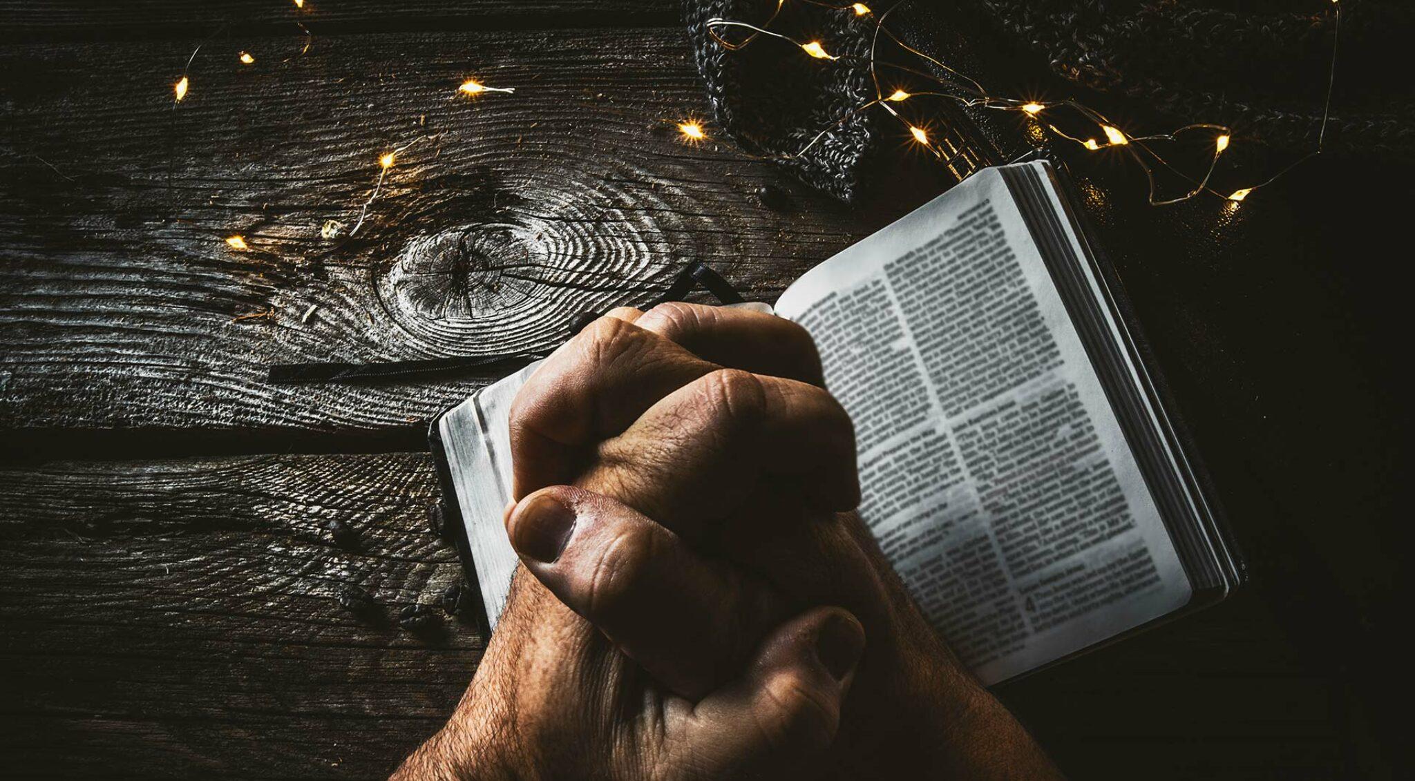 Bild betender Hände und Gebetsbuch