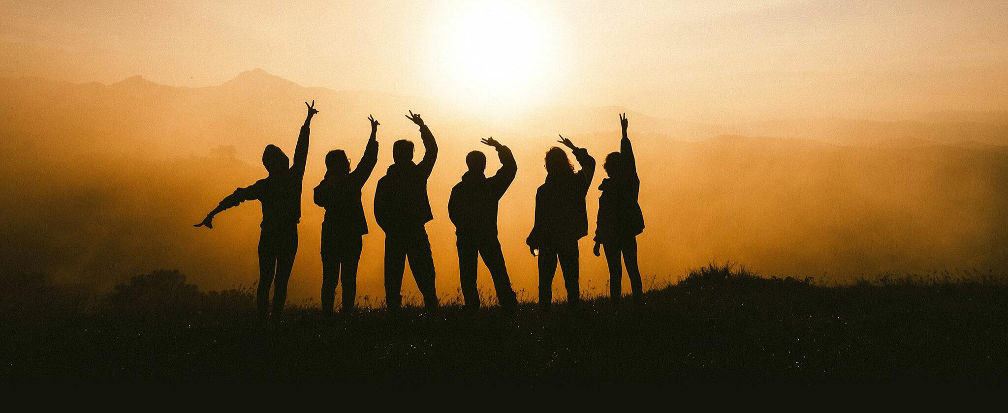 Silhoutten sechs glücklicher Personen vor einem Sonnenuntergang.