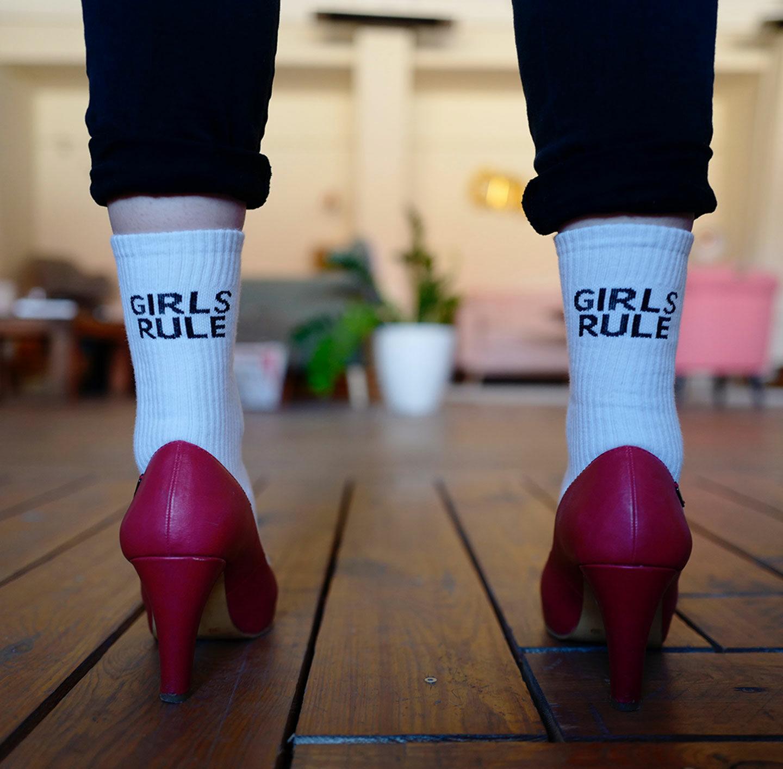 """Frau in pinken High Heels trägt Socken mit Aufschrift """"Girls rule""""."""