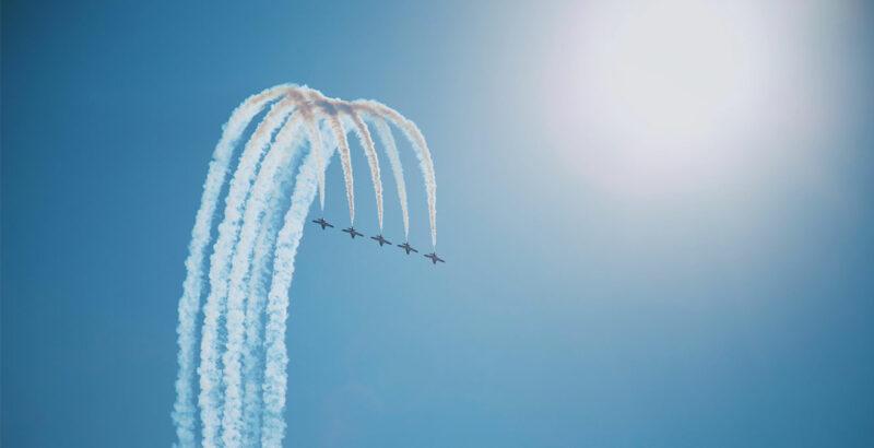 Fünf Flugzeuge fliegen synchron einen Bogen.
