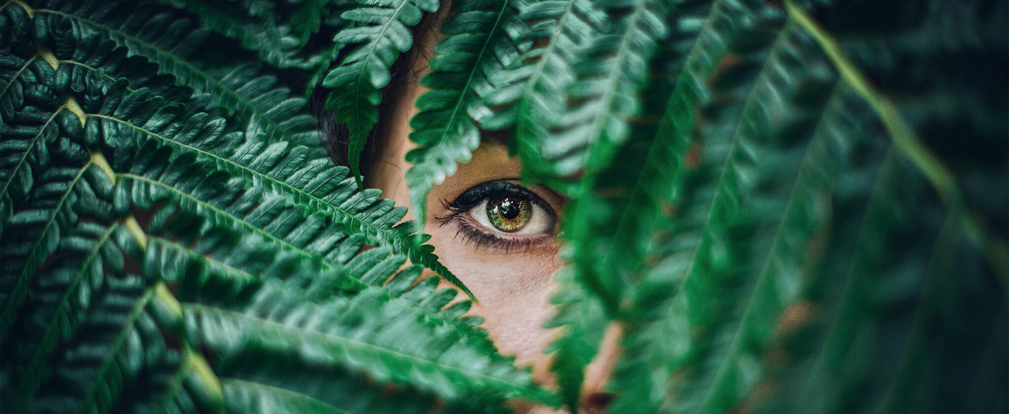 Gesicht einer Frau hinter grünen Blättern.