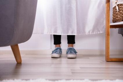 Bild eines Kindes, das sich hinter einem Vorhang versteckt