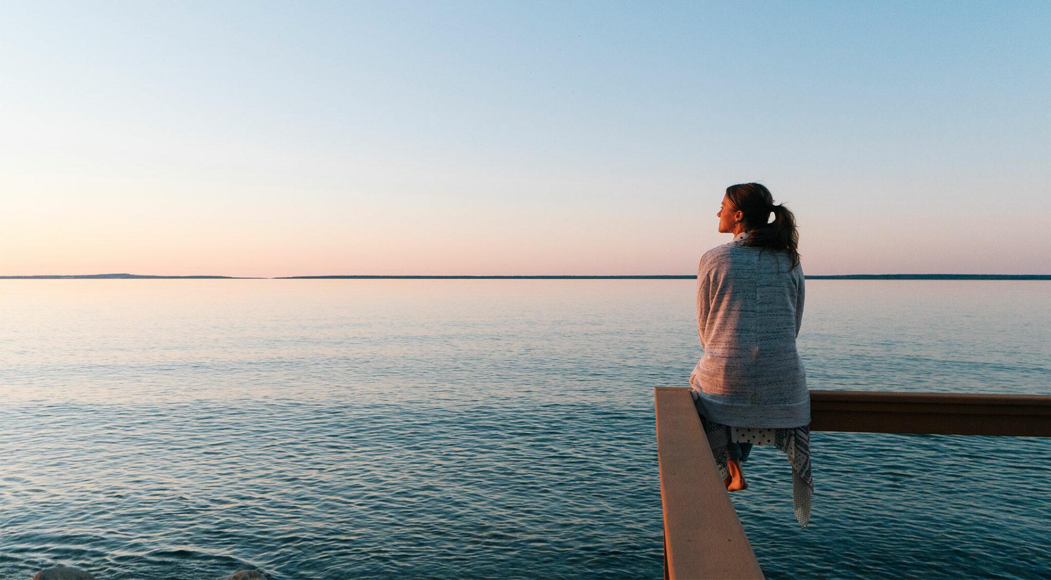 Eine Frau sitzt in der Abenddämmerung an einem See.