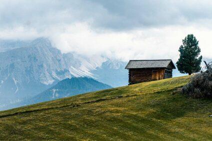 Einsames Hüttchen vor Bergkulisse.
