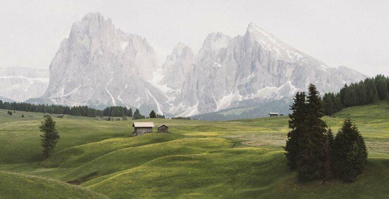 Grüne Wiesen vor Bergkulisse.