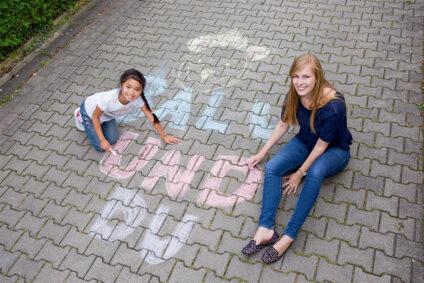 """Eine Frau und ein Kind malen den Schriftzug """"Balu und du"""" mit Kreide auf den Boden."""