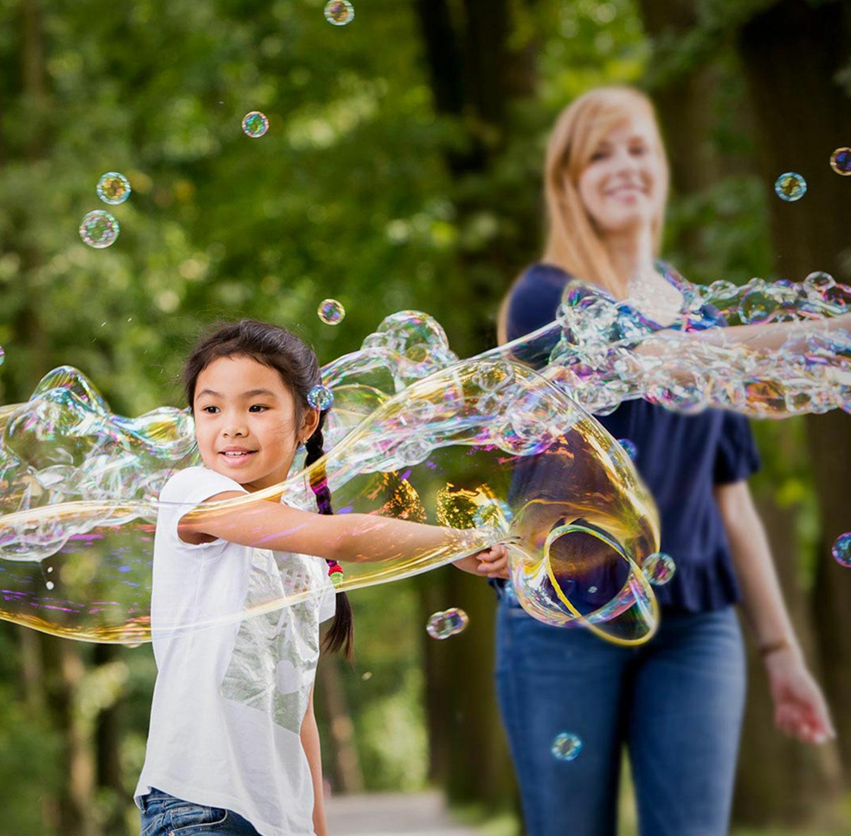 Eine Frau und ein Kind ziehen große Seifenblasen.