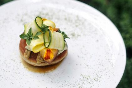 Stilvoll angerichtetes Gericht aus Rouelle Cendree, Emmerlangosh, Pfirsichsenf und Zucchini.