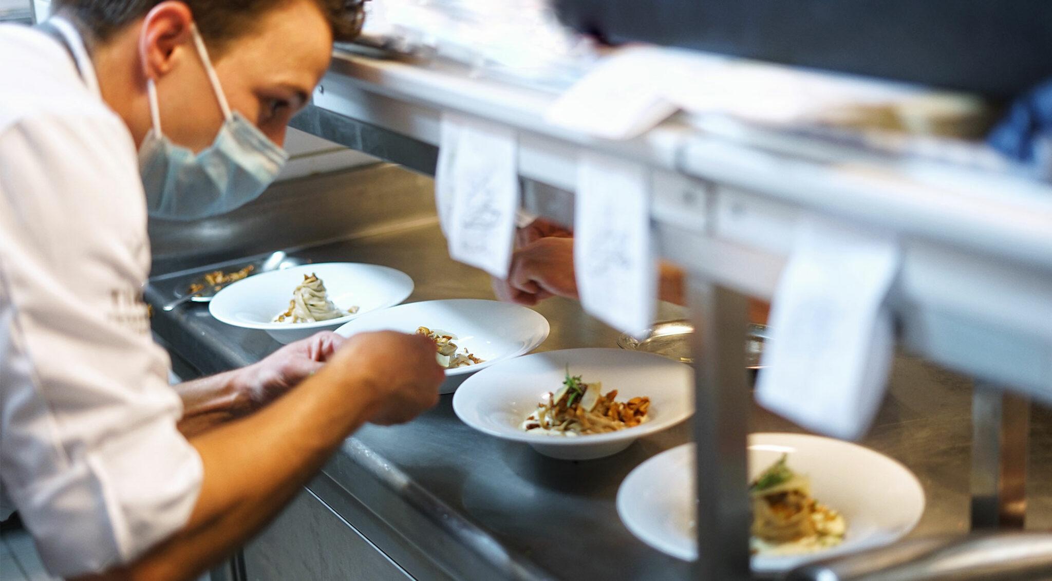 Ein Koch stellt fertige Gerichte auf den Küchenpass.