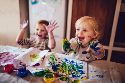 Zwei glückliche Kinder beim Malen.