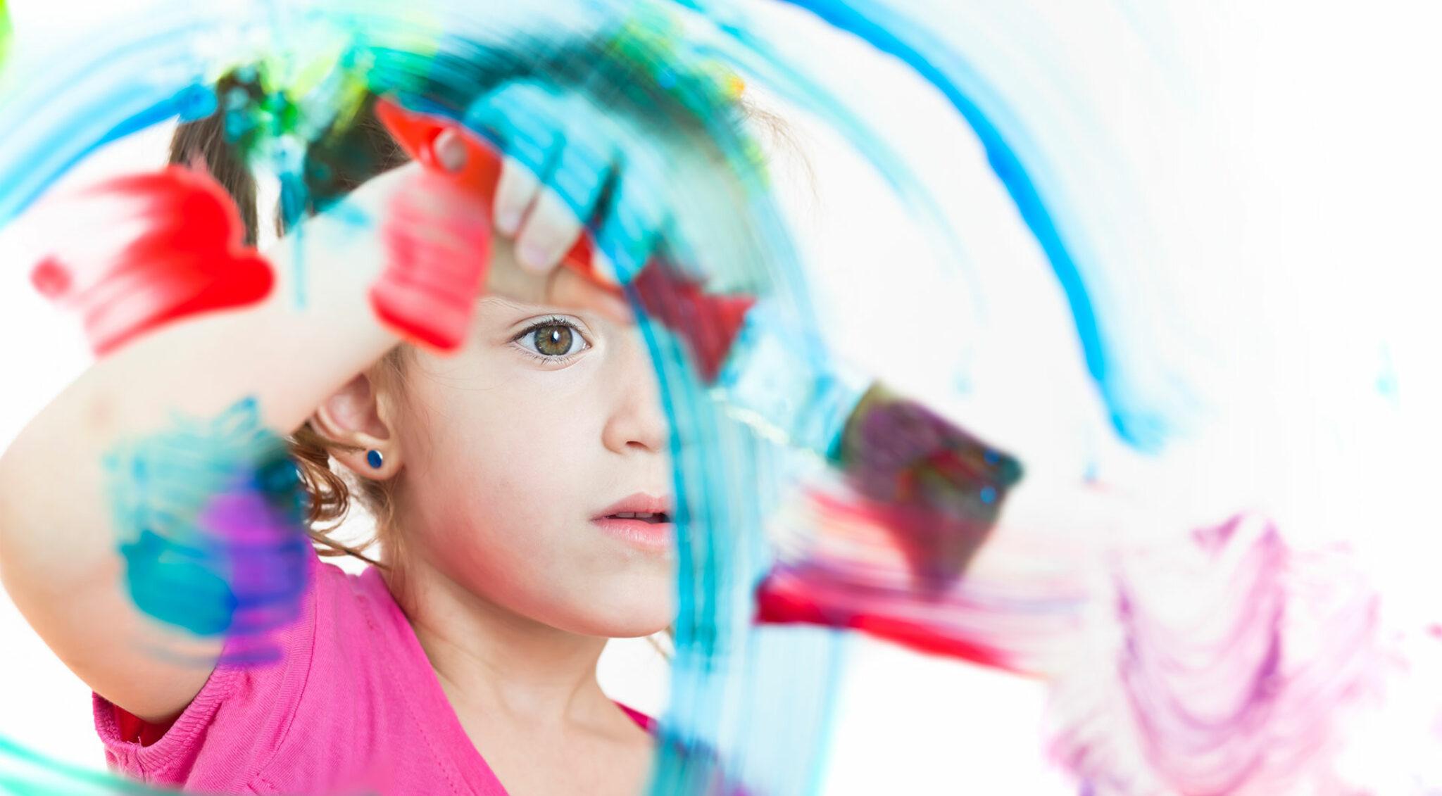 Ein Kind malt mit einem großen Pinsel.