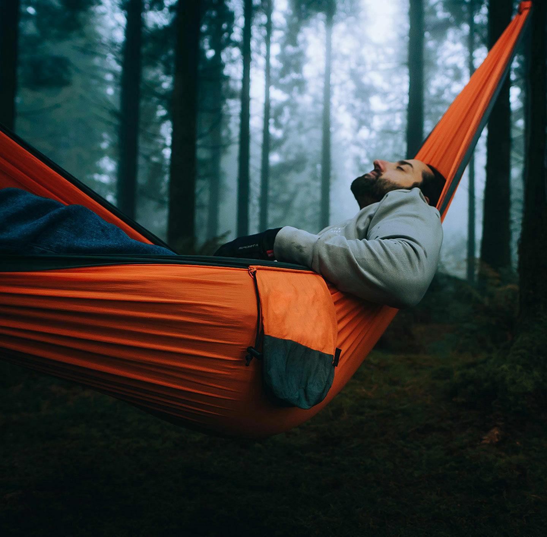 Ein Mann entspannt in einer Hängematte im Wald.
