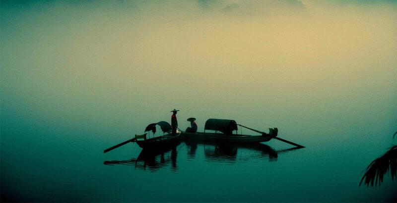 Zwei asiatische Fischer in ihren Ruderbooten, umgeben von neblig-grüner Kulisse.