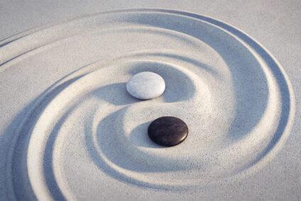Yin und Yang-Zeichen, mit zwei Steinen in Sand gemalt.
