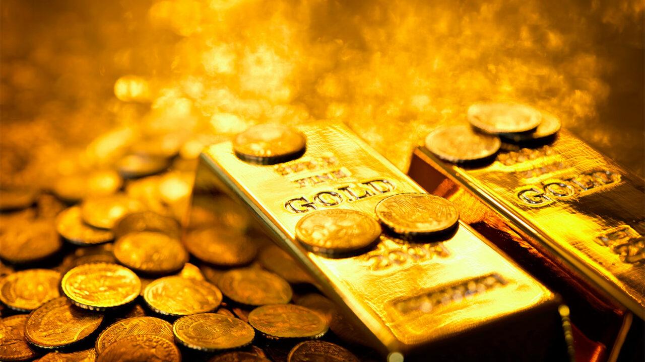 Zwei Goldbarren und Goldmünzen.