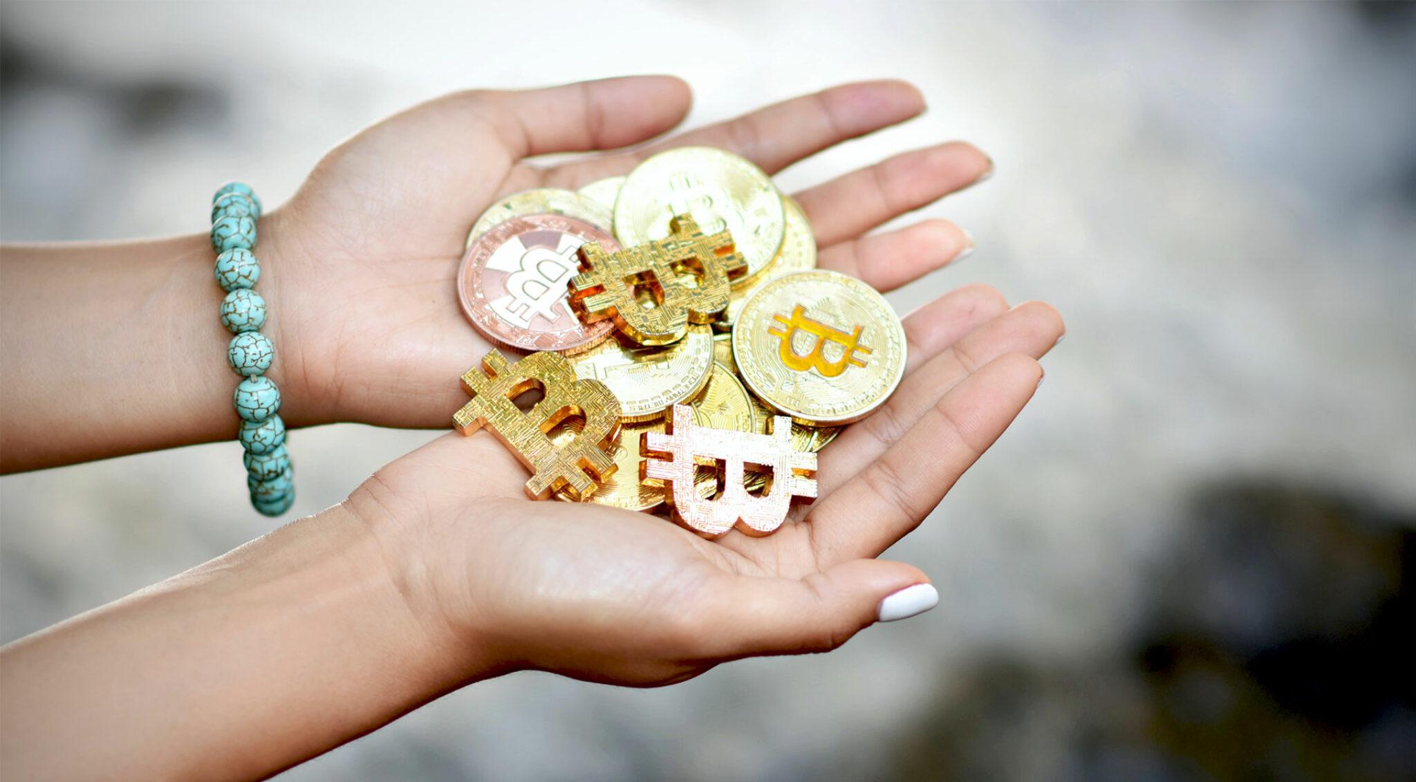 Frau hält Goldmünzen in den offenen Händen.