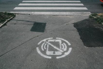 Das Piktogramm eines duchgestrichenen Smartphones, auf die Straße gesprüht.