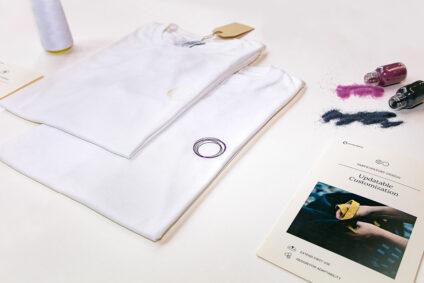 Zwei weiße T-Shirts, mit Accessoires präsentiert.