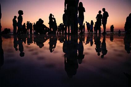 Die Konturen vieler Menschen vor einem Sonnenuntergang.
