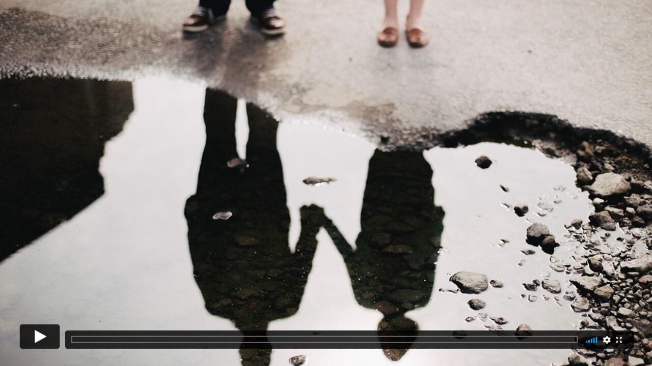 Spiegelung eines Paares in einer Wasseroberfläche.
