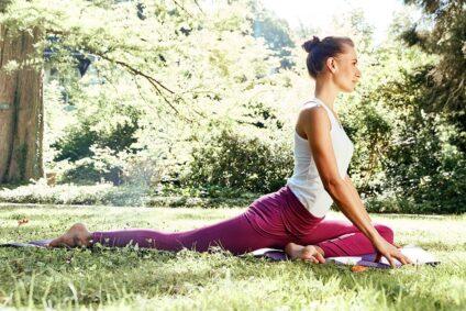 Eine Frau macht im Grünen Yoga.