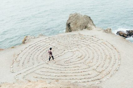 Auf einer Klippe über dem Meer läuft eine Person durch ein aus Steinen gelegtes Muster.
