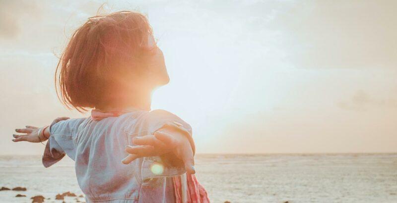 Frau am Meer blickt in die Sonne und streckt die Arme zur Seite aus.