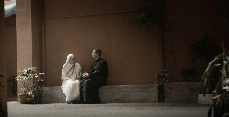 In einer Filmszene spricht Mutter Teresa mit einem Geistlichen.