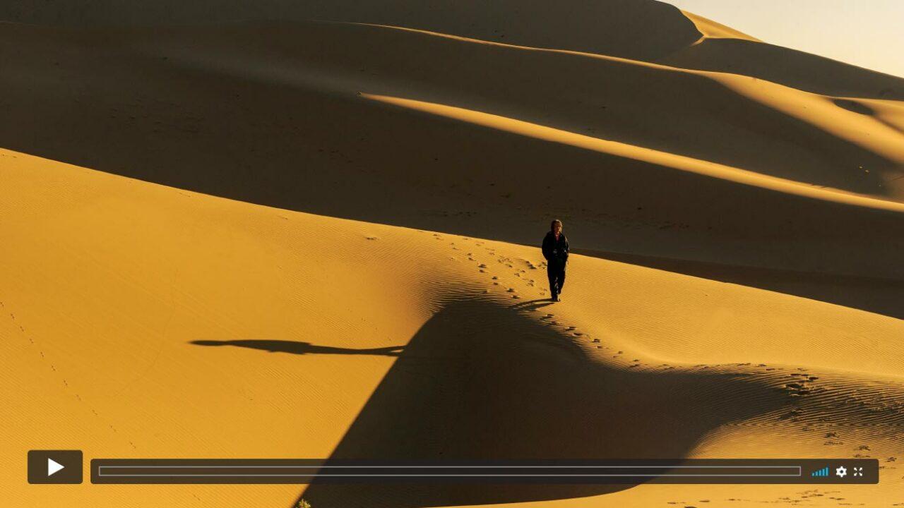 Ein einsamer Mann läuft über Dünen in der Wüste.